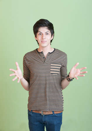 Hispanic teen with open hands over green background