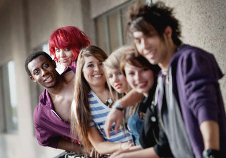 focuses: Punk rock looking teens smile at the camera as the camera focuses on the back two individuals. Editorial
