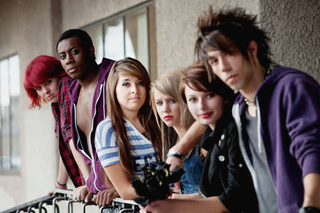 focuses: Attractive young teen punks look at the camera as it selectively focuses on the brunette in the middle.