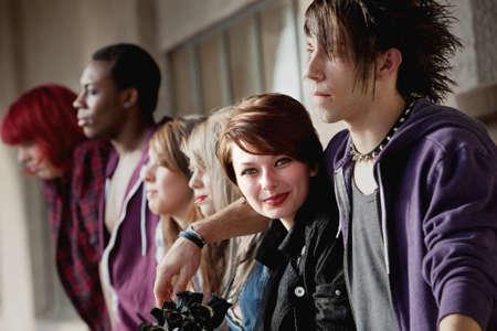 pandilleros: Un grupo de punks adolescentes atractivos mirar a la distancia como una niña sonríe para la cámara.