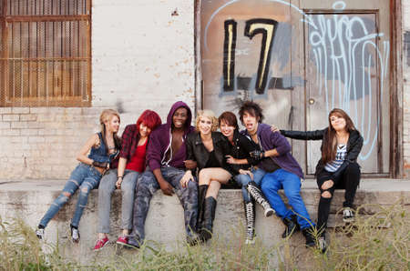 Group of attractive young punk teens hang out behind an abandoned building downtown.