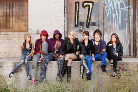 Bunch of punk teens look to the camera with serious expressions behind an abandoned building.