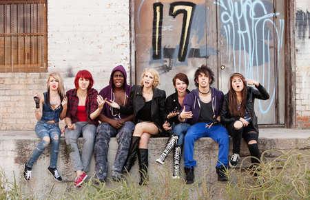 pandilla: Un grupo de jóvenes punks adolescentes gritando airadamente que su foto está tomada. Editorial