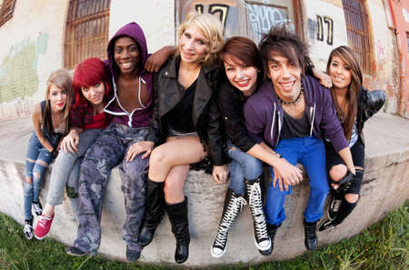 handsome teenage guy: Attractive group of teen punks smile for the camera as they sit behind an abandoned warehouse.