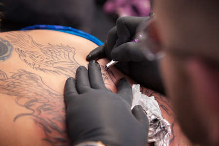 Tattoo expert draws outlined design on a womans back Stock Photo