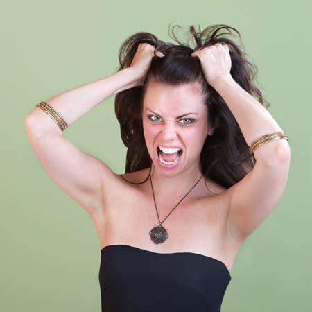 젊은 좌절 된 여자는 녹색 배경 위에 그녀의 머리를 끌어 스톡 콘텐츠