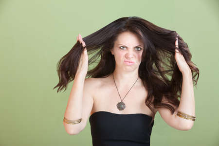 messy hair: Unhappy woman plays with her hair over green background