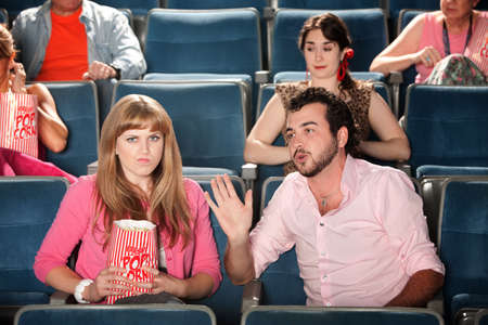 Young man talks out loud with annoyed woman in theater