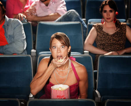 theater audience: Shocked Caucasian woman eats popcorn in theater