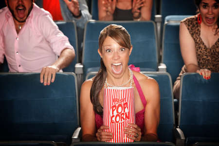 fear woman: Screaming woman with popcorn bag in theater Stock Photo
