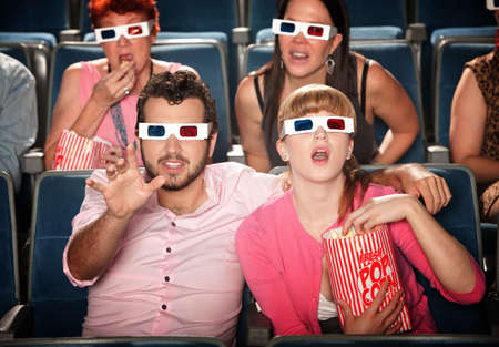 Amazed Caucasian couple with 3D glasses in theater seats photo