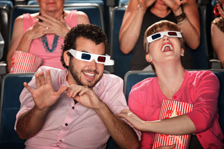 Happy Caucasian couple with 3D glasses in theater photo