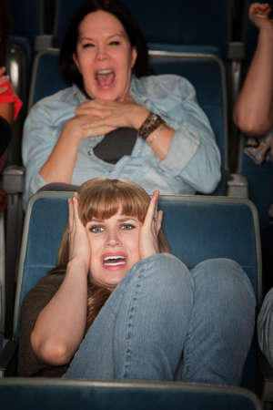 Screaming women watch scary movie in theater photo