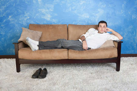 Young Caucasian man rests on sofa with shoes on floor photo