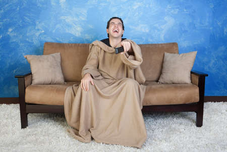 loud: Young Caucasian man in blanket with remote control laughs out loud Stock Photo