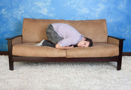 curledup: Angry young Caucasian man in fetal position on sofa