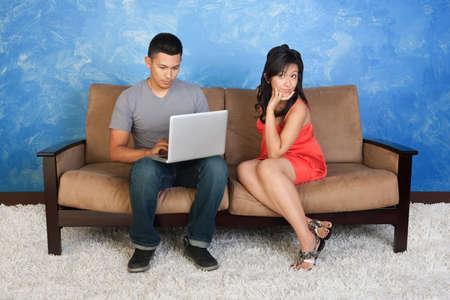 Unhappy Hispanic girlfriend with boyfriend using laptop