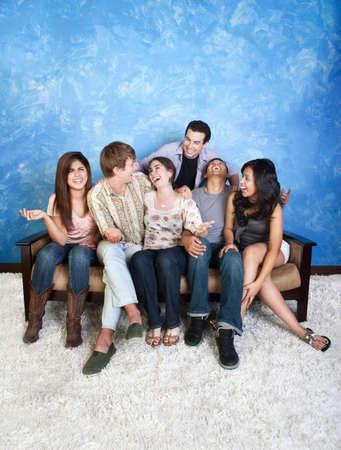 Groep van zes vrienden lachen op de bank
