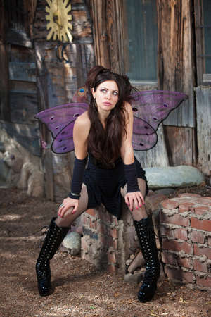 fishnet: Serious fairy relaxes in rustic scene with hands on knees