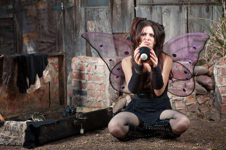 Unhappy Caucasian fairy relaxing on ground with magic eight ball