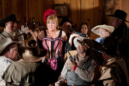 The entire saloon points their guns at the bargirl who was just caught cheating.