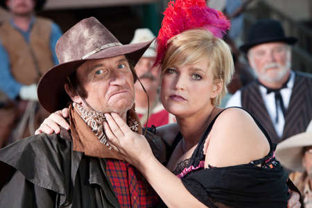 A mean looking cowboy is caressed by the local bargirl. Stock Photo - 11653965