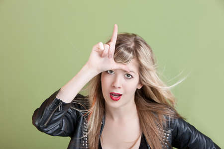 loser: Young woman makes loser sign on her forehead over green background Stock Photo