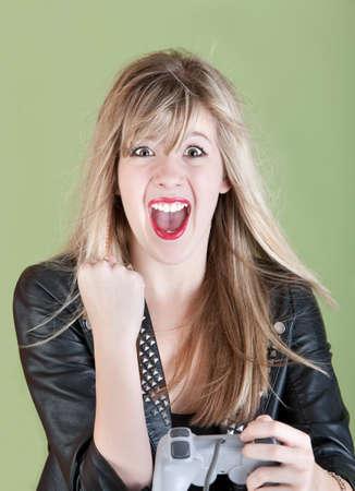 ビデオゲームのコント ローラーの若いのレトロなスタイルの白人女性が彼女の拳をポンプします。 写真素材
