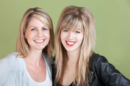 adult 80s: Happy mom and daughter smile over green background
