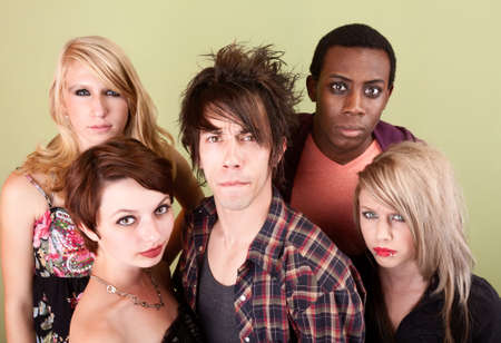 Five angry urban teens stare at the camera in front of a green studio wall.