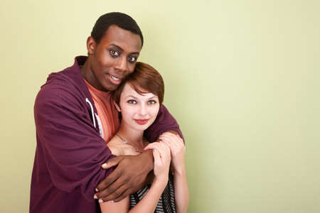 Young mixed race couple hug lovingly in front of a green wall in the studio.