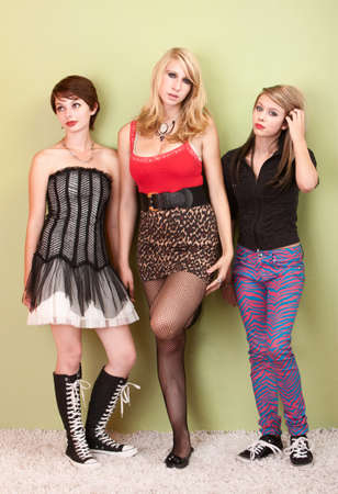 Three attractive teen girl punks stare at the camera with a bored expression.