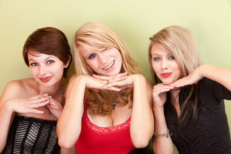 Three beautiful teen girls pose with their heads on their hands in a portrait.