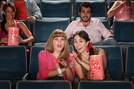 theater audience: Friends with a bag of popcorn in theater Stock Photo