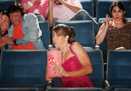 Woman snacks on popcorn with group seated in theater photo