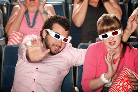 Scared Caucasian couple with 3D glasses in theater photo