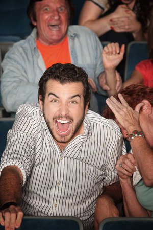 loud: Young Caucasian laughs out loud in theater  Stock Photo