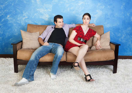Smiling young Caucasian man with frustrated woman sit on sofa