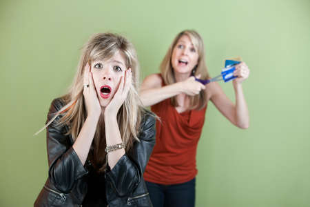 Mom threatens to cut daughter's credit cards with a scissors Stock Photo - 11647186