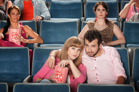 Young romantic couple with popcorn bag at movie in theater photo