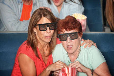 Tense Caucasian women watch 3D movie in theater photo