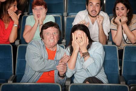 asustado: Grupos de gente asustada en el cine Foto de archivo