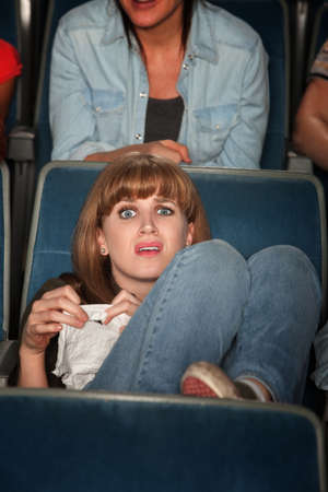 Young Caucasian woman holding tissue weeps in theater photo