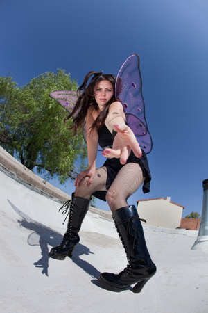 goth girl: Beautiful fairy on rooftop makes hand gestues to come close