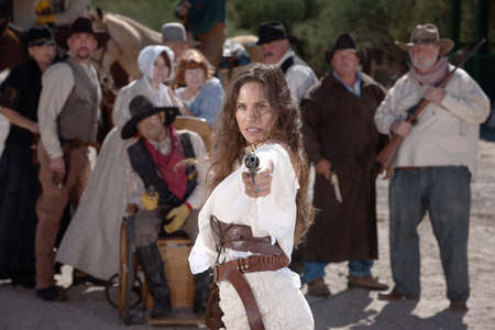 Strong old west woman points her gun defiantly photo
