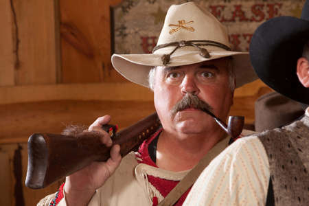 outdoorsman: An old west fur trapper shoulders his rifle with a pipe in his mouth.