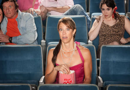 Horrified people watch movie in theater photo