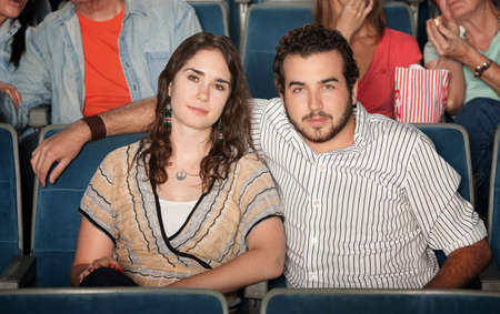 Young caucasian couple watch movie in theater photo