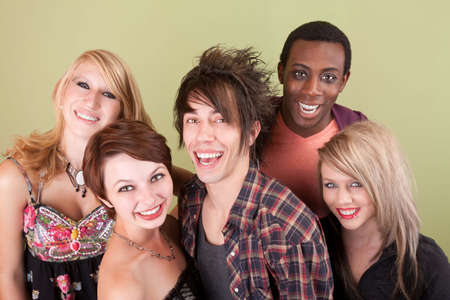 Five urban dressed teens laugh towards the camera in front of a green studio wall. photo