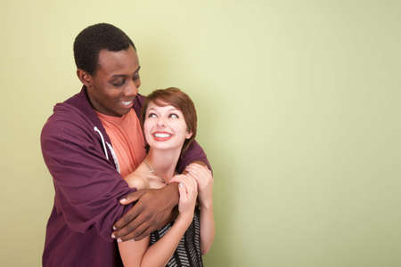 happy teens: Young, loving mixed race couple look into each others eyes in front of a green wall. Stock Photo